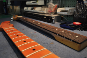 Zwei Gitarrenhälse liegen bereit für die Neubundierung